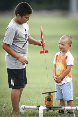 Mike Moore | The Journal Gazette Silas Clemets, 4, right, patiently watches his cousin, Damien Starkey, 13, load his rocket onto the launchpad Sunday during a club launch for the Summit City Aerospace Modelers at the Concordia Theological Seminary.