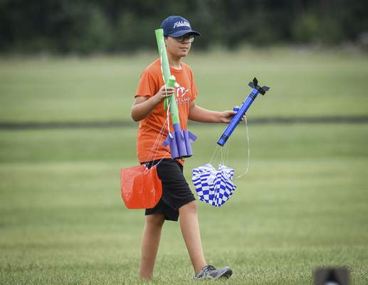 Mike Moore | The Journal Gazette Josh Braun, 11, retrieves his rockets on Sunday after launching them at the Concordia Theological Seminary with the Summit City Aerospace Modelers rocket club.