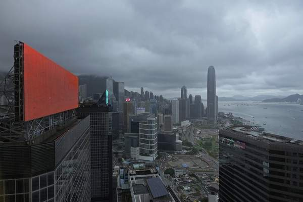 A red advertisement board is seen with backdrop of Hong Kong's business district in Hong Kong Monday, July 19, 2021. (AP Photo/Vincent Yu)