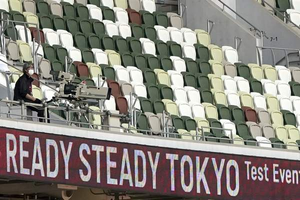 Associated Press A TV cameraman sits beside empty spectators' seats during a track and field test event in May at the National Stadium in Tokyo. No fans will be allowed at any of the venues in Tokyo.