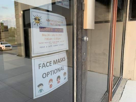 Ashley Sloboda | The Journal Gazette  A sign taped to the entrance of the Administration Building indicates masks are optional at East Allen County Schools.
