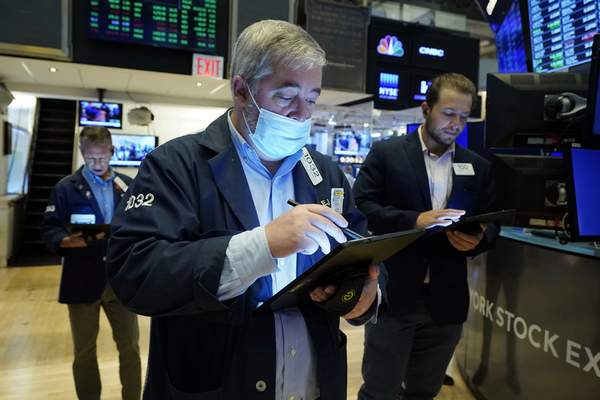 Edward McCarthy, center, works with fellow traders on the floor of the New York Stock Exchange, Tuesday, July 20, 2021. (AP Photo/Richard Drew)