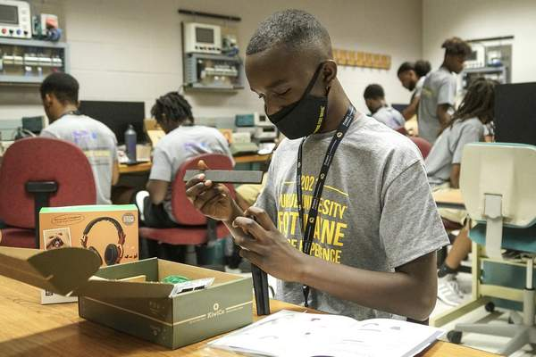 Jefferson Middle School student JaKaj Rich, 13, builds a pair of headphones Tuesday while taking part in  the  College Experience, a program designed to encourage young men of color to consider college after high school.
