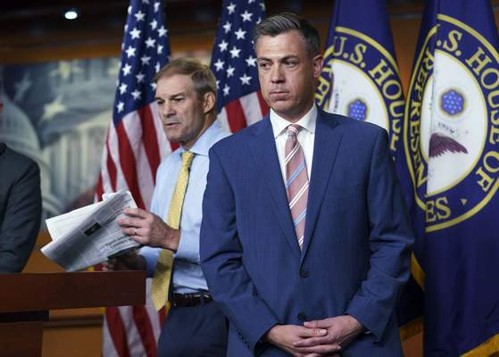 Rep. Jim Banks, R-Ind., center, and Rep. Jim Jordan, R-Ohio, left, exchange places at the podium during a news conference after House Speaker Nancy Pelosi rejected the two who were picked by House Minority Leader Kevin McCarthy, R-Calif., for the committee investigating the Jan. 6 Capitol insurrection at the Capitol in Washington, Wednesday, July 21, 2021. (AP Photo/J. Scott Applewhite)