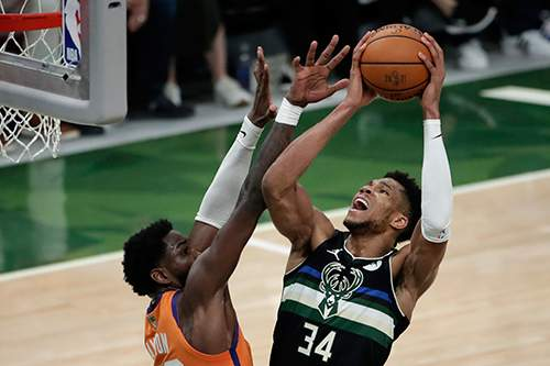 Milwaukee Bucks forward Giannis Antetokounmpo (34) shoots against Phoenix Suns center Deandre Ayton during the second half of Game 6 of basketball's NBA Finals Tuesday, July 20, 2021, in Milwaukee. (AP Photo/Aaron Gash)