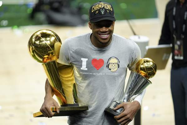 Milwaukee Bucks forward Giannis Antetokounmpo smiles while holding the NBA Championship trophy, left, and Most Valuable Player trophy after defeating the Phoenix Suns in Game 6 of basketball's NBA Finals in Milwaukee, Tuesday, July 20, 2021. The Bucks won 105-98. (AP Photo/Paul Sancya)