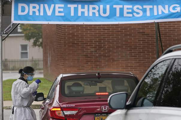 FILE - In this Wednesday Oct. 21, 2020, file photo a health worker prepares to administer a COVID-19 swab at a drive-thru testing site in Lawrence, N.Y. (AP Photo/Seth Wenig, File)