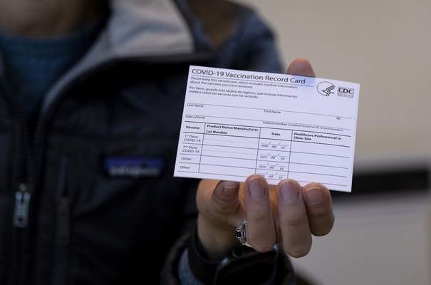 FILE - In this Jan. 10, 2021 file photo, Sarah Gonzalez of New York, a Nurse Practitioner, displays a COVID-19 vaccine card at a New York Health and Hospitals vaccine clinic in the Brooklyn borough of New York. (AP Photo/Craig Ruttle, File)