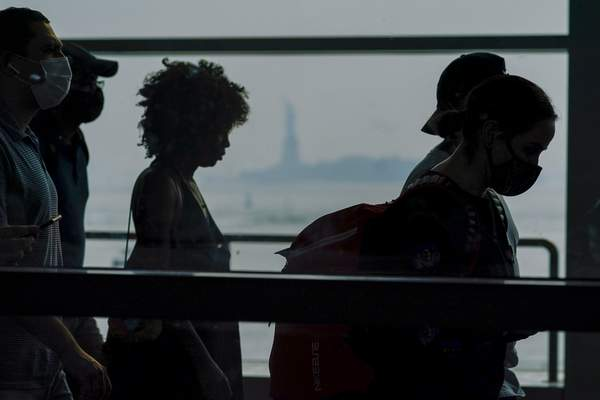 Staten Island ferry commuters walk past a view of the Statue of Liberty seen through haze, Tuesday, July 20, 2021, in New York. (AP Photo/Mary Altaffer)