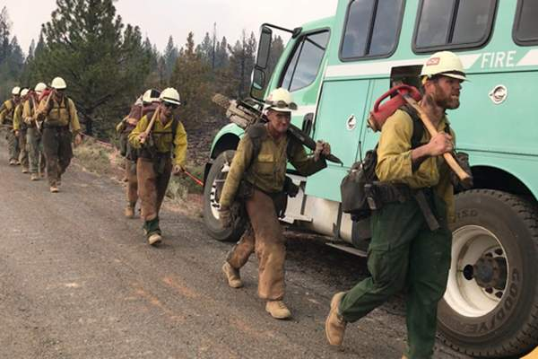 In this photo provided by the Bootleg Fire Incident Command, a handcrew walks to engage the Bootleg Fire in southern Oregon on Monday, July 19, 2021. (Bootleg Fire Incident Command via AP)