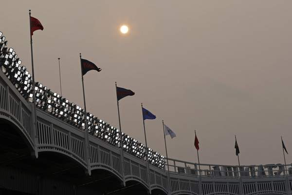 Smoke from Western wildfires dims the sun before the Philadelphia Phillies played New York Yankees in a baseball game Tuesday, July 20, 2021, in New York. (AP Photo/Adam Hunger)