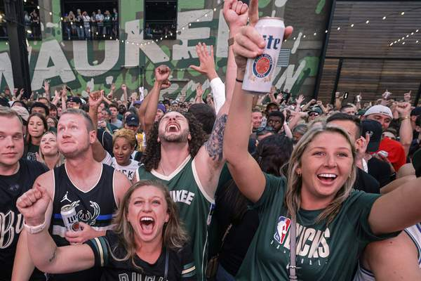 Fans watch television coverage of Game 6 of the NBA basketball finals between the Milwaukee Bucks and the Phoenix Suns on Tuesday, July 20, 2021, in Milwaukee. (AP Photo/Jeffrey Phelps)