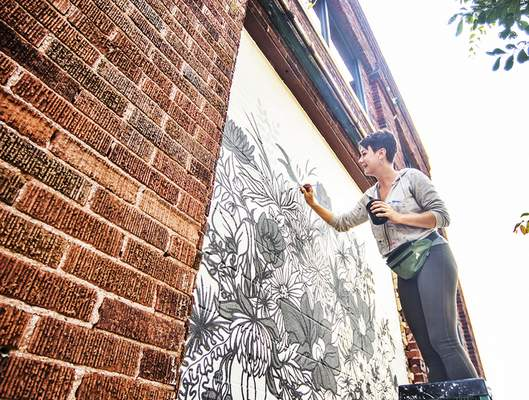 Katie Fyfe | The Journal Gazette Julie Wall works on a mural Wednesday at the Elysean event venue on Main Street downtown.