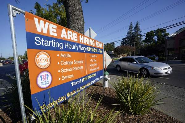 A car passes a hiring banner in Sacramento, Calif., Friday, July 16, 2021. (AP Photo/Rich Pedroncelli)
