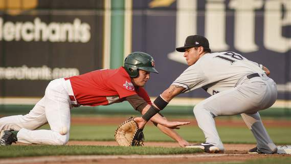 Mike Moore | The Journal Gazette  Chris Givin reaches for the bag as Dayton's Victor Ruiz fields Thursday at Parkview Field.