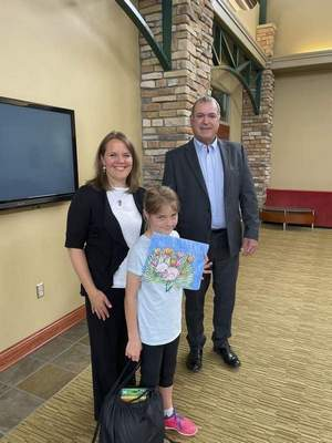 Julie Bloomfield, a home-schooled student, shows off her award-winning artwork with her mother, Mindy Bloomfield, and KREMC President and CEO Kurt Carver.
