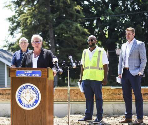 Katie Fyfe | The Journal Gazette  Community Development Director Nancy Townsend speaks Monday about a new homebuilding partnership. Looking on are, from left, Mayor Tom Henry, Pastor Lewis King and Andrew Gritzmaker, Habitat for Humanity CEO.