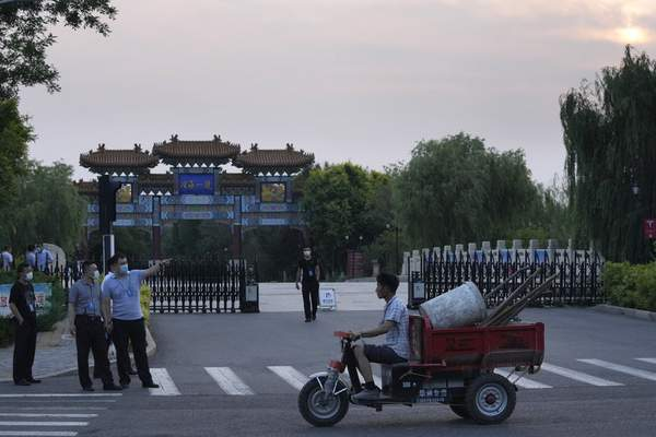 A worker transporting work tools pass by security personnel outside the Tianjin Binhai No. 1 Hotel where U.S. and Chinese officials are expected to hold talks in Tianjin municipality in China on Sunday, July 25, 2021. (AP Photo/Ng Han Guan)