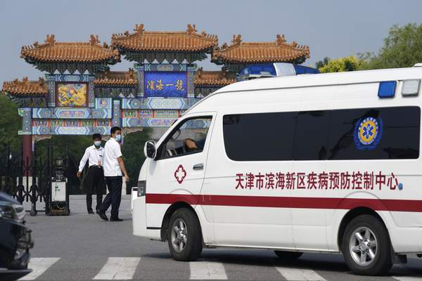 Security guards watch as a vehicle for the epidemic control center pulls up to the entrance into the Tianjin Binhai No. 1 Hotel where U.S. and Chinese officials are expected to hold talks in Tianjin municipality in China Monday, July 26, 2021. (AP Photo/Ng Han Guan)