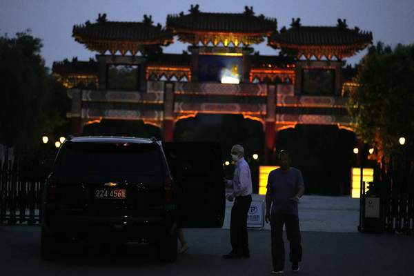 A man exits a U.S. embassy car outside the Tianjin Binhai No. 1 Hotel where U.S. and Chinese officials are expected to hold talks in Tianjin municipality in China on Sunday, July 25, 2021. (AP Photo/Ng Han Guan)