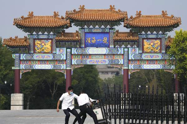 Security guards pull a barrier into the Tianjin Binhai No. 1 Hotel where U.S. and Chinese officials are expected to hold talks in Tianjin municipality in China Monday, July 26, 2021. (AP Photo/Ng Han Guan)