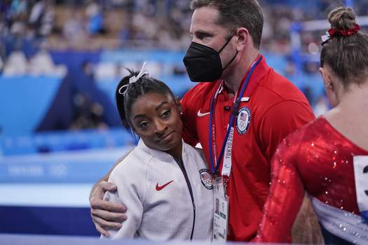 Tokyo Olympics Artistic Gymnastics Coach Laurent Landi embraces Simone Biles, after she exited the team final with apparent injury, at the 2020 Summer Olympics, Tuesday, July 27, 2021, in Tokyo. (AP Photo/Gregory Bull) (Gregory Bull STF)