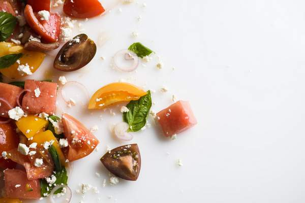 This image released by Milk Street shows a recipe for watermelon salad with tomato, basil and goat cheese.