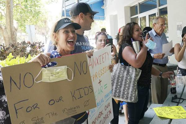 Associated Press Joann Marcus of Fort Lauderdale, left, shouts as she listens to the Broward County School Board's emergency meeting Wednesday in Fort Lauderdale, Fla. A small but vocal group spoke vehemently against masks.