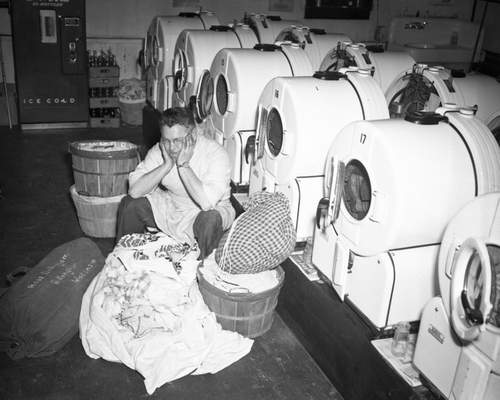 Tom Portman sits at his self-service laundry on Fairfield Avenue with washing machines that were rendered unusable during the water emergency.