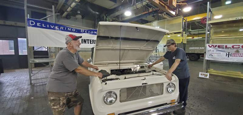 Courtesy of Harvester Homecoming  Former Fort Wayne International Harvester/Navistar employees Syl Engelmann, left, and Greg Maroney work on a 1966 Sportop Scout 800 in the former engineering complex on Meyer Road that will be on display during Harvester Homecoming's third festival Aug. 6-7.