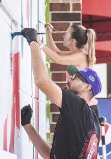 Katie Fyfe | The Journal Gazette  Matthew Plett works on a mural at Jefferson Pointe with the assistance of his wife Amanda Plett Tuesday.