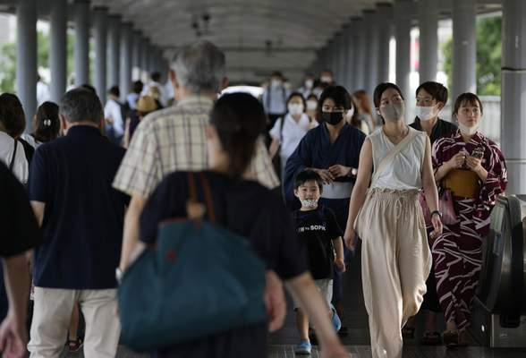 People wearing protective masks pass through a pedestrian bridge Friday, July 30, 2021, in Yokohama, south of Tokyo. Japan is set to expand the coronavirus state of emergency in Tokyo to neighboring prefectures including Saitama, Chiba and Kanagawa, where Yokohama is located, and the western city of Osaka as infections surge to new highs while the capital hosts the Olympics. (AP Photo/Kiichiro Sato)