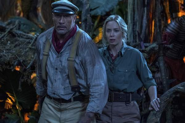 This image released by Disney shows Emily Blunt, right, and Dwayne Johnson in a scene from Jungle Cruise. (Disney via AP)