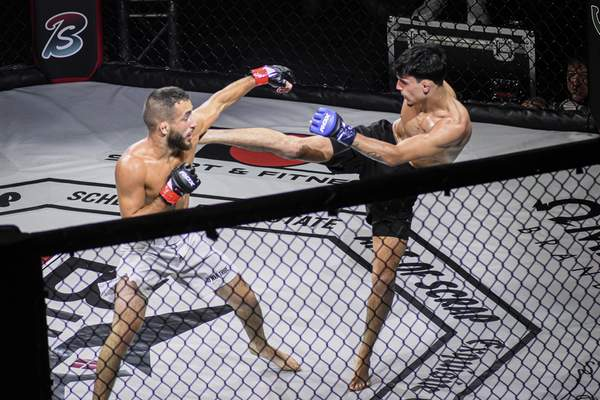 Mike Moore   The Journal Gazette Local fighter Dominic Heath, right, delivers a kick Saturday to Tyler Smythe in the amateur flyweight bout at Memorial Coliseum.
