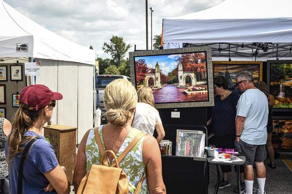 Mike Moore | The Journal Gazette Guests attending the Covington Art Fair on Saturday check out wall art on display.