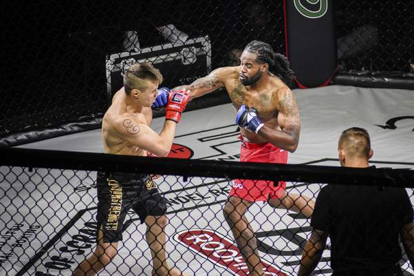 Mike Moore | The Journal Gazette MMA fighter Anthony Fleming , right, delivers a punch to opponent Kyle Broadwater Saturday during Art of Scrap, Mixed Martial Arts event at Memorial Coliseum.