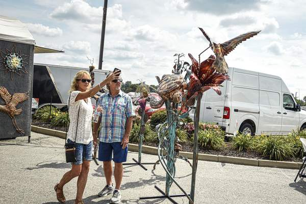 Mike Moore | The Journal Gazette A woman takes a photo of a metal sculpture on display at the Covington Art Fair on Saturday.