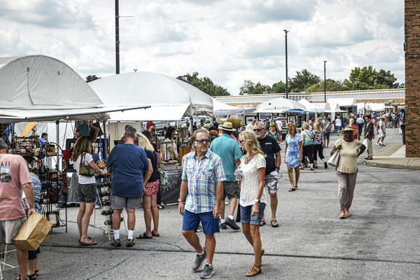 Mike Moore | The Journal Gazette Visitors and tents fill the parking lot at Covington Plaza off West Jefferson Boulevard on Saturday.