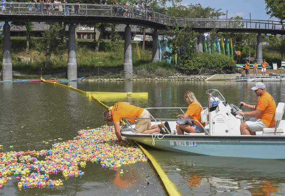 Michelle Davies   The Journal Gazette Officials pull ducks from the St. Marys River at the finish line at Promenade Park on Saturday afternoon for the 33rd annual Weigand Construction Duck Race to benefit SCAN.