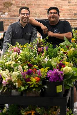 Associated Press Steven Dyme, owner of Flowers for Dreams, poses with employee Kevin Cervantes. Dyme's company has a $15-an-hour minimum wage.