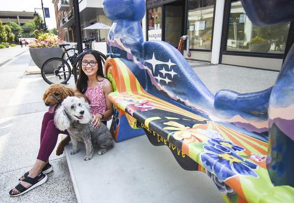 Katie Fyfe | The Journal Gazette Madeline Phuong sits next to the LoveSeat she painted on Columbia Street with her poodle Redd, short for Reddington, 1, and her miniature poodle Roxie, 11.