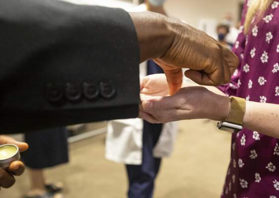 Associated Press Rev. Don Ajoko, chaplain at Our Lady of the Lake Regional Medical Center in Baton Rouge, La., anoints the hands of health care workers from around the country who have arrived to bolster the staff amid a COVID-19 spike.