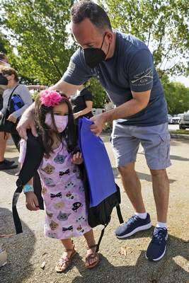 Alberto Gordon helps his daughter Alina, 3, try on a book bag during a bag and school supply give away at the office of Miami-Dade County Commissioner Joe Martinez, Friday, July 30, 2021, in Miami. (AP Photo/Wilfredo Lee)
