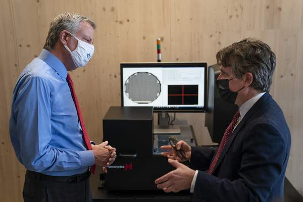 FILE - In this April 28, 2021 file photo, New York Mayor Bill de Blasio, left, speaks with Matthew Putman, co-founder and CEO of Nanotronics, during a facility tour before a ribbon-cutting ceremony to mark the opening of a Nanotronics manufacturing center at the Brooklyn Navy Yard in the Brooklyn borough of New York. (AP Photo/John Minchillo, Pool)