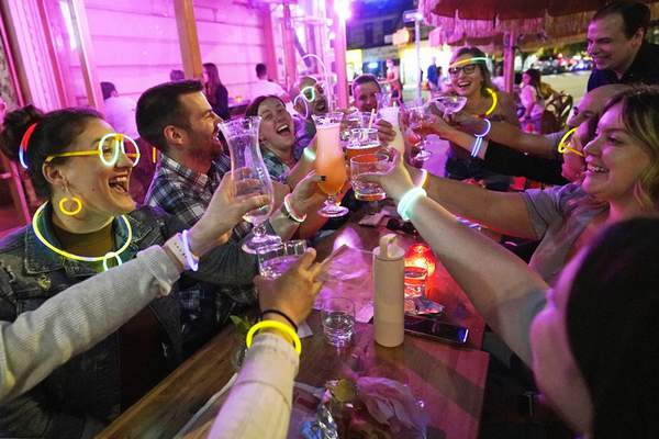 FILE: In this May 17, 2021 file photo, Emily Baumgartner, left, and Luke Finley, second from left, join friends from their church group in a birthday toast to one of the members, upper right, during their weekly Monday Night Hang gathering at the Tiki Bar on Manhattan's Upper West Side, in New York. (AP Photo/Kathy Willens, File)