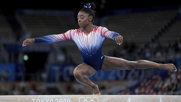 """Associated Press photos Simone Biles of the United States performs on the balance beam  Tuesday at the Summer Olympics in Tokyo. Biles returned to compete in the event after pulling out of previous events citing a case of the """"twisties."""""""