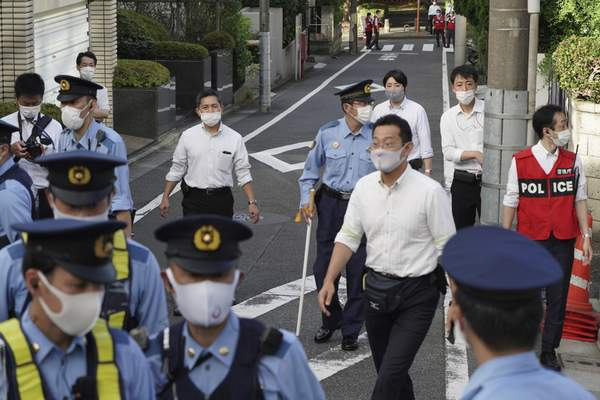 Police officers gather in front of the Poland's Embassy in Tokyo before a van with Belarusian Olympic sprinter Krystsina Tsimanouskaya leaves Wednesday, Aug. 4, 2021. Tsimanouskaya plans to seek refuge in Europe after accusing team officials of trying to force her to leave the Tokyo Games early. (AP Photo/Kantaro Komiya)