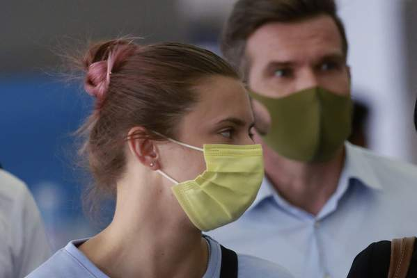 Belarusian Olympic sprinter Krystsina Tsimanouskaya, left, arrives at Narita International Airport in Narita, east of Tokyo Wednesday, Aug. 4, 2021. Tsimanouskaya plans to seek refuge in Europe after accusing team officials of trying to force her to leave the Tokyo Games early. (AP Photo/Koji Sasahara)