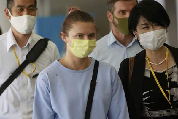 Belarusian Olympic sprinter Krystsina Tsimanouskaya, center, arrives at Narita International Airport in Narita, east of Tokyo Wednesday, Aug. 4, 2021. Tsimanouskaya plans to seek refuge in Europe after accusing team officials of trying to force her to leave the Tokyo Games early. (AP Photo/Koji Sasahara)