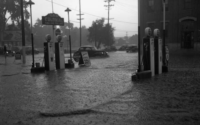 July 16, 1947:A whitecap wave shows the depth of the water in the filling station driveway at Colonial Gas & Oil Co. at Brakenridge and Calhoun streets. (Journal Gazette file photo)